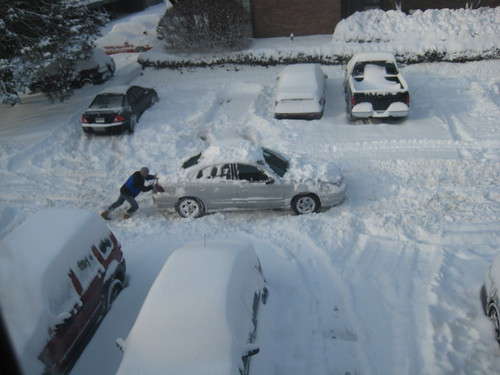 Man pushing car in snow